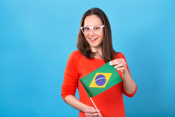 Happy young woman with glasses with the flag of Brazil on a blue background. A football fan.