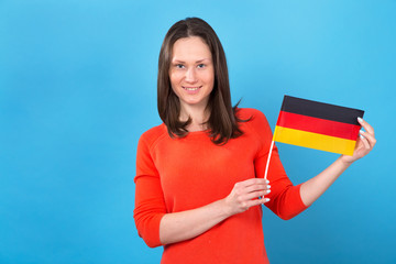 Beautiful brunette woman with the flag of Germany on a blue background.