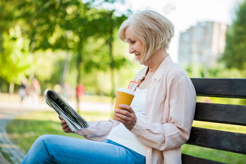 Adult woman sitting in park and reading newspapers.