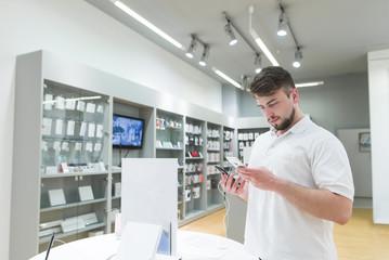 Handsome bearded man is in the electronics store in the phone department and chooses a smartphone. Buyer buys a smartphone in a technology store. Purchase of a smartphone in a store.