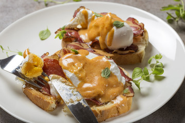 Eggs Benedict- toast, ham, poached eggs, and delicious buttery hollandaise sauce