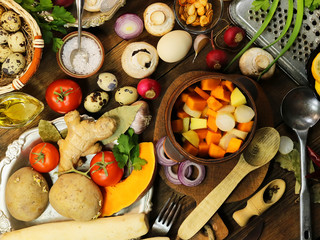 cut mushrooms, pumpkin and potatoes in a clay pot. cooking healthy food. spices and ingredients. wooden background.