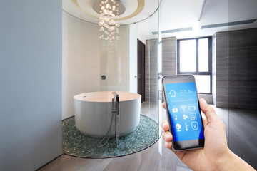 mobile phone with smart home app in modern bathroom