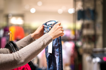 Woman holding jeans and shopping in fashion clothing store. Person choosing trendy skinny jeans in clothes shop.