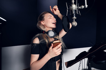 Create something new! Side view portrait of the attractive young woman music artist with mobile phone recording a song in the music studio.