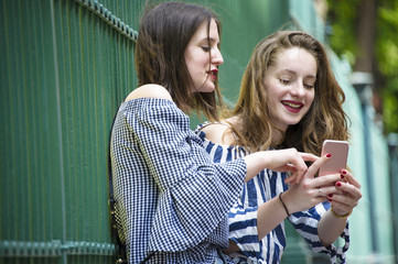 Two young and beautiful hipster woman are sitting on a fence and looking pictures on smart phone. BFF. Street fashion, working conception.