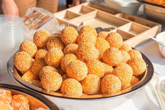 a bunch of sesame balls served on a metal bowl on a farm street market