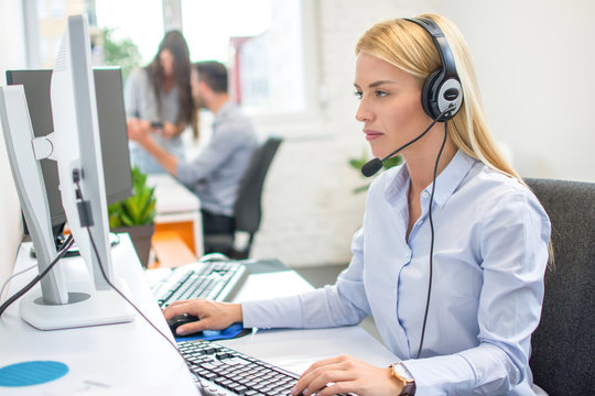 Young woman call center operator in headset in business office