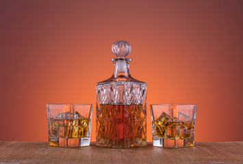 Old fashion glass and carafe with the alcohol, whisky drink on warm, dark orange background and wood