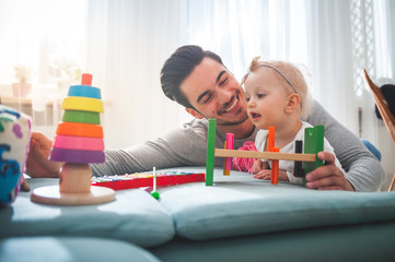 Handsome father with his child playing together using toys on sofa