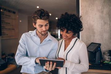 Restaurant business partners using digital tablet