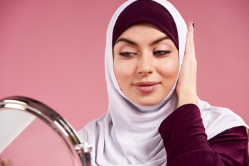 Attractive Arab woman in hijab looks in mirror.