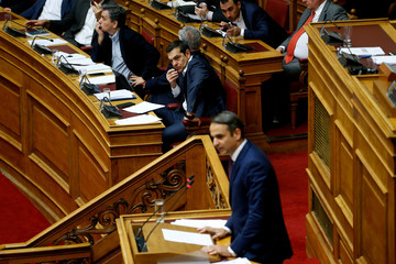 Main opposition New Democracy conservative party leader Kyriakos Mitsotakis addresses lawmakers as Greek Prime Minister Alexis Tsipras looks on (C, background) during a parliamentary session about government's negotiations with country's creditors in Athen