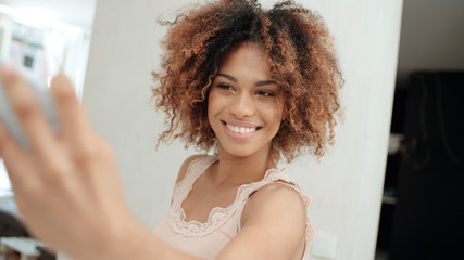 Attractive young black woman making selfie in the kitchen.