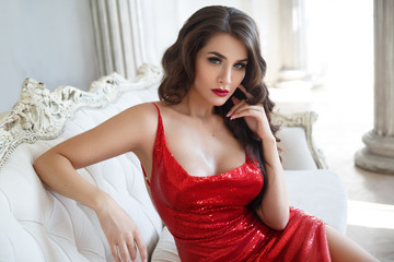 A smart slender girl in an expensive red shiny dress in an interior with columns.