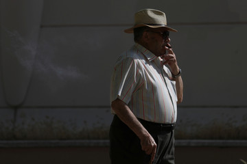 An elderly man smokes a cigar as he takes a walk during a sunny day in Madrid