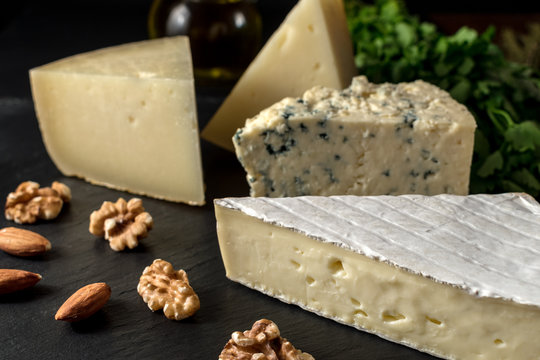 Different kinds of cheeses on black stone board with nuts and herbs.