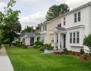 Neighborhood city block: homes, lawns and sidewalk.