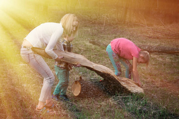 Mother with daughter and son are pulling a large log in the nature. Interaction of mother and child. Active rest. Toned.