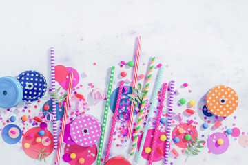 Cocktail straws, jar caps, confetti and candies in a colorful party concept, dessert and catering supplies on a light background with copy space from above