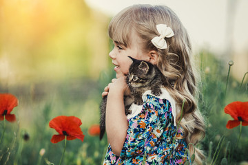 little girl with blond hair standing up holding a striped kitten. The kitten sits on the child's shoulder