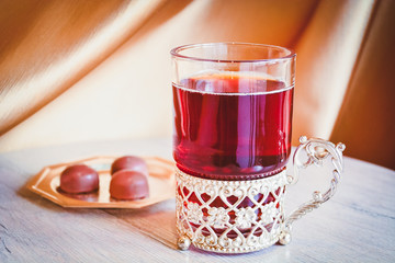 Black tea in clear glass with metal elements (in oriental style)  next to a metal plate with candies