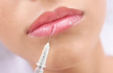 Young woman getting lip injection in beautician salon, closeup