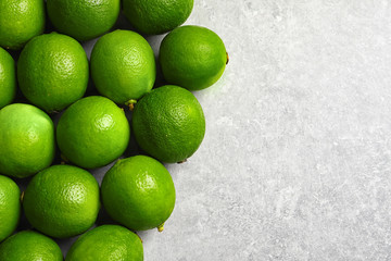 Fresh ripe green limes on light background