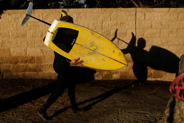 Surfer Gary Clisby carries his homemade foil board to the beach in Del Mar, California