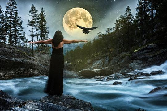 Frau im schwarzen Kleid bei Vollmond am Fluss