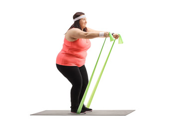 Overweight woman exercising with a rubber band on a mat