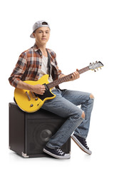 Teenage boy with an electric guitar sitting on an amplifier
