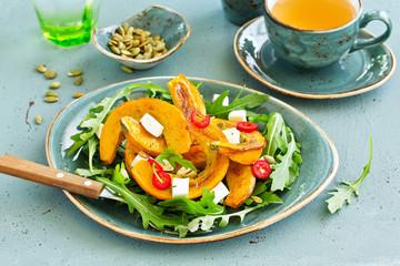 Salad with slices of baked pumpkin, feta, pepper.