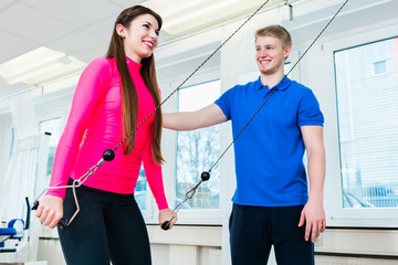 Woman in health club getting instructions for using workout equipment by her instructor