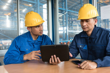 Two Asian skilled workers analyzing information displayed on tablet PC while sitting down indoors