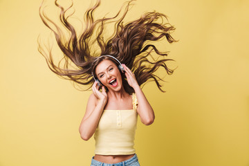 Image of amusing woman 20s singing and having fun with shaking hair while listening to music via headphones, isolated over yellow background