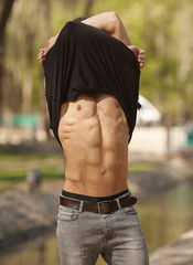 Very sexy young man showing abdominal muscles with taking off his t-shirt on a blurred background. Handsome, brutal macho in shorts, looking at camera.