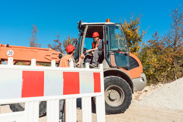 Construction worker starting road works on site with machine