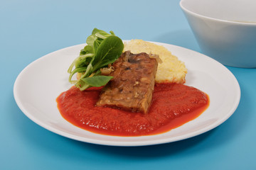 Tempeh with tomato sauce and dumplings on a blue