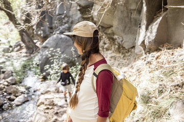 A mother waits for her kid on a hiking trail