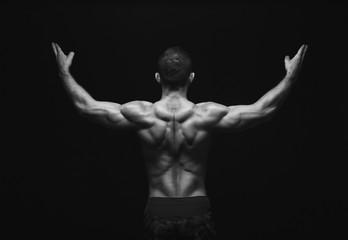 Unrecognizable man shows strong back muscles closeup