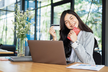 happy woman holding credit card and using laptop and smartphone shopping website online, shopping concept