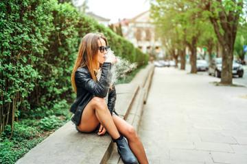 Pretty brunette woman smoke electronic cigarette outdoor