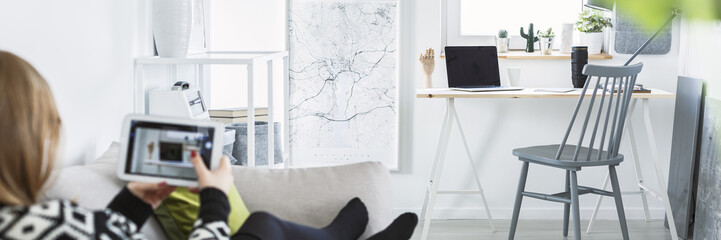 Woman sitting on the sofa and taking photo of home office corner in white flat interior with map poster and fresh plants