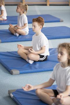 Children in relaxing meditation class