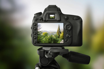 DSLR camera on a tripod is taking a picture of the landscape