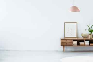 Pink lamp above wooden sideboard