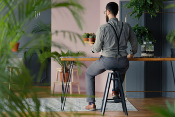 Gardener holding succulents at wooden table in stylish interior with plants