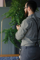 Hipster in grey shirt interested in biology holding plant at home