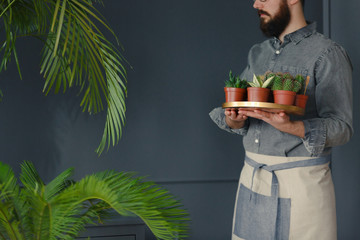 Man with beard and in work suit holding succulents in grey orangery